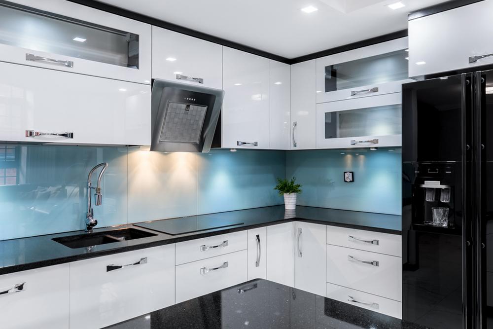 Белая кухня с синим фартуком и черной столешницей