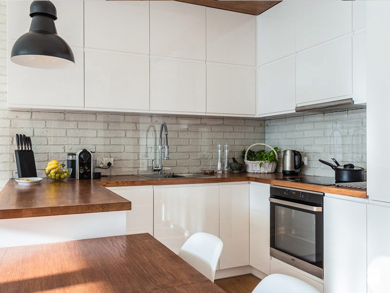 белая кухня с коричневой столешницей в интерьере